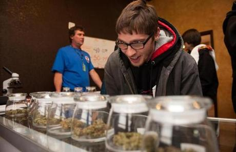 Tyler Williams of Blanchester, Ohio, selected marijuana varieties to buy on New Year's Day at a dispensary in Denver.